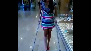 girl with a legcast crutching in the mall