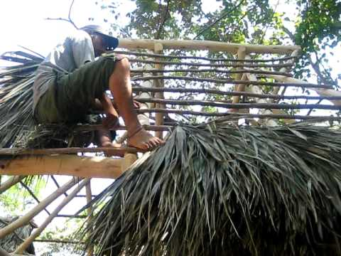 Thatching a roof with palm fronds
