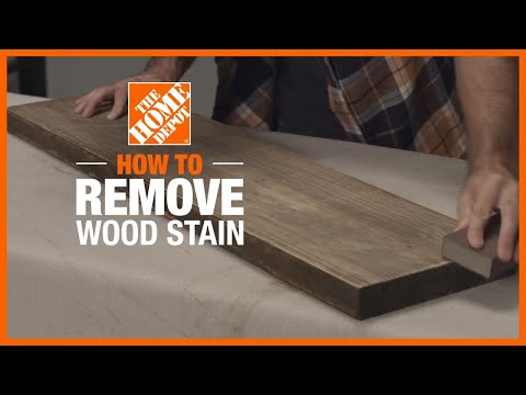 A person removes stain from wood furniture with a scraper.