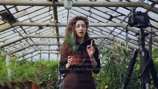 Professional female gardener is recording tutorial about gardening with camera standing inside width=