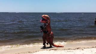 Comtemplative dinosaur playing the Jurassic Park theme on the bagpipes at the beach.