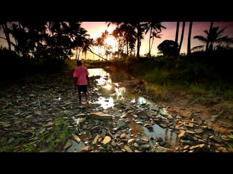 Boy walking along a rocky stream in Africa at sunset.
