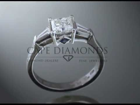 3 stone ring,cushion diamond,2 diamonds a side,one blue stone in front,platinum band,engagement ring