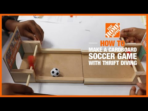 A father helps a daughter build a soccer game project.