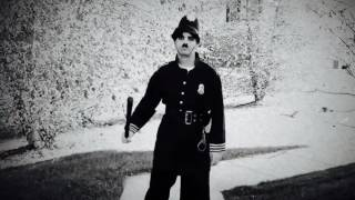 Charlie Chaplin the Keystone Cop, on his beat.
