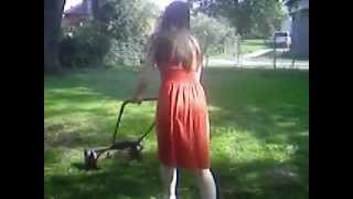 windy orange dress 1 cutting the grass mowing the lawn wind blowing walking pushing mower woman mows