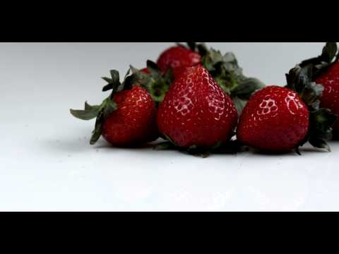 Royalty Free Stock Footage of Single strawberry rolling away from the bunch.